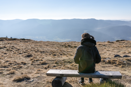 Young unrecognizable woman sitting an a bench on a mountain peak. Osser, upper bavarian forest, germany.