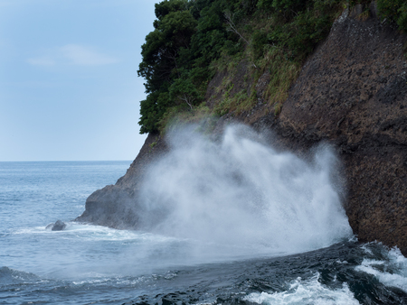 Sea water blowing out from a side hole cave Stock Photo