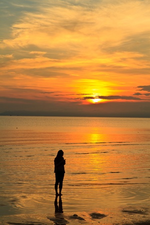 Young woman standing  in sea and looking to a sun Stock Photo
