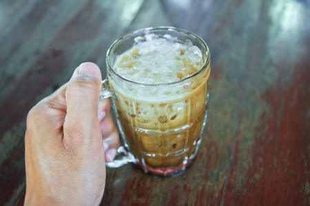hand hold Coffee  glass  on table photo