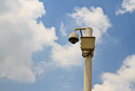 High tech overhead security camera with a  blue sky  photo