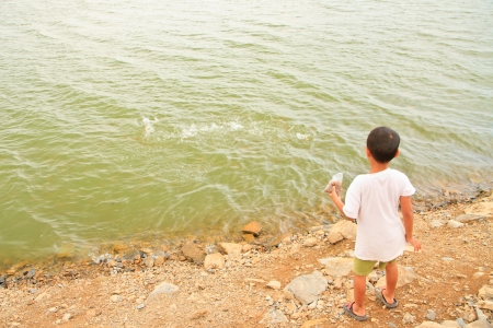 Boy give feed for fish in DAM Stock Photo - 14856311