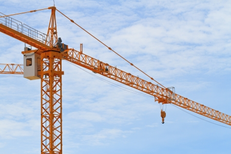 Yellow construction crane against blue sky photo