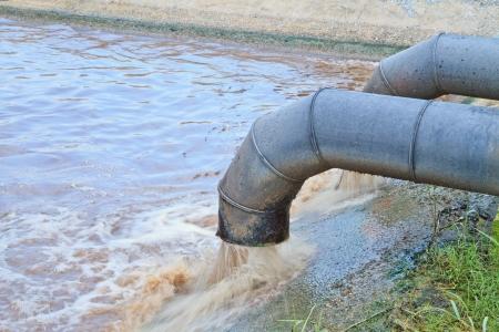 contaminacion ambiental: El agua sucia fluye de una tubería de desechos tóxicos de producción Foto de archivo