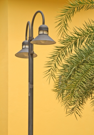 street lamp in front of the wall of yellow brick photo
