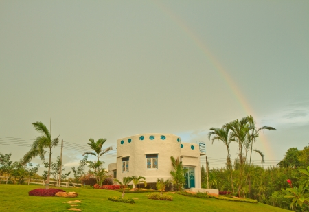 A new house with a garden in a rural area and  rainbow