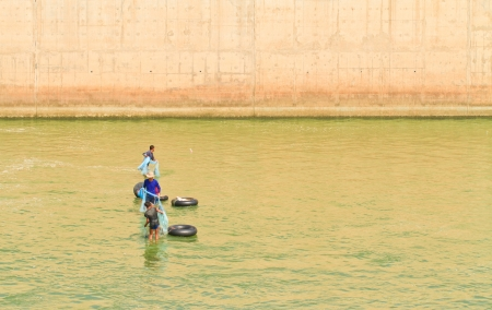 throwing fishing net at pasak dam, Thailand photo