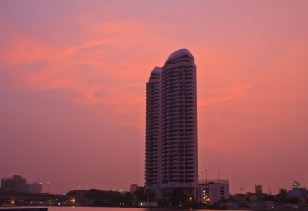 High rise building and sunset near river on  sky background