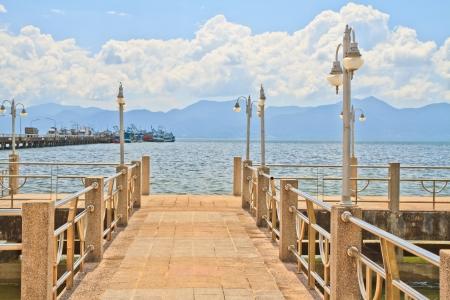 bridge in to the sea and sea port , mountain background Stock Photo - 17077091