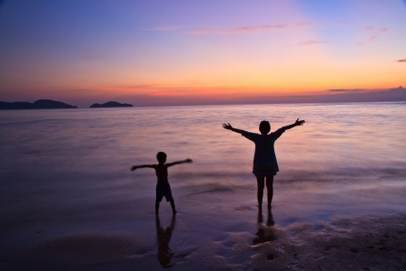 Silhouette of mother  and a child at the coast photo