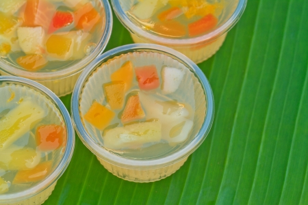 fruit jelly small cup on green banana leaf photo