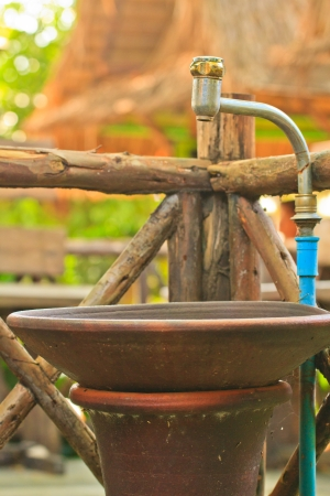 Old washbowl  with tap and pipe  and out on a wood fence background Stock Photo - 17125571