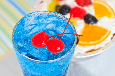 Close up un c�ctel azul y cereza en vidrio y fresco pastel con frutas photo