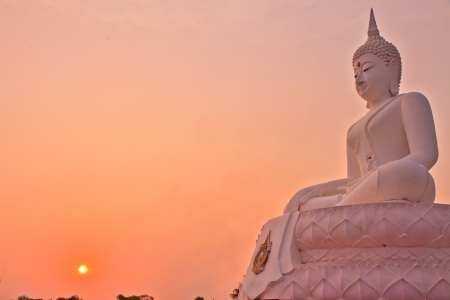 The buddha image and sunset  on  sky background photo