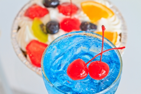 Close up one blue cocktail and cherry in glass and fresh fruited cake photo