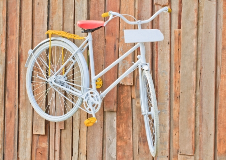 classic white bicycle hanging on old wooden wall and white plate  photo