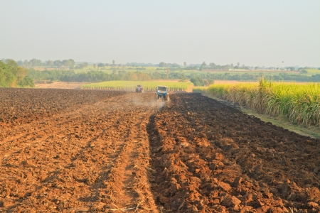 Small scale farming with tractor and plow in field photo