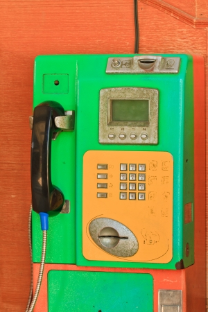 Old public telephone Coin orange and green color on wood wall Banco de Imagens