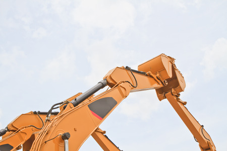 The scoop of a backhoe on a cloudy sky background photo