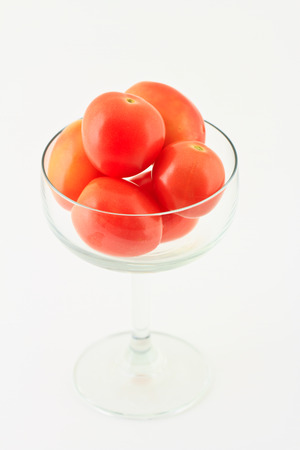 Tomatoes in glass on white background Stock Photo