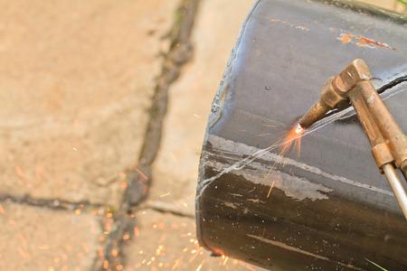 cut through: Worker using an Gas cutting torch to cut through metal in factory.