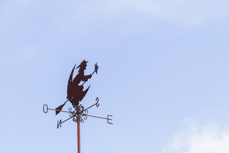 Witch weather vane on blue sky background