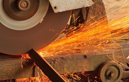 Close up a rotating circular saw is cutting a metal