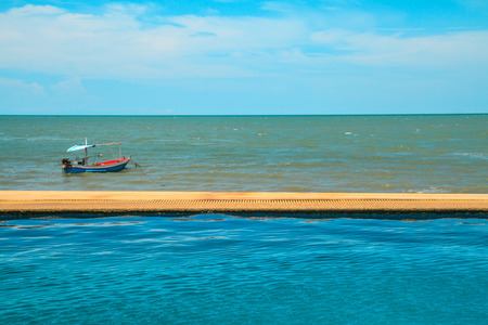 Luxury swimming pool a tropical resort and boat on sea, Blue sky background 스톡 콘텐츠