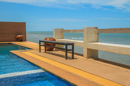 Wooden bench seat and pool on stone floor near sea and blue sky. Stock Photo