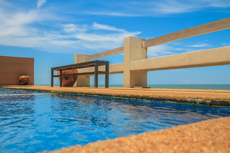 Wooden bench seat and pool on stone floor near sea and blue sky. Banco de Imagens