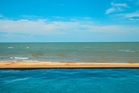Luxury swimming pool a tropical resort and sea on blue sky background