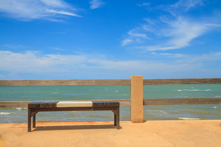 Wooden bench seat on stone floor near sea and blue sky.
