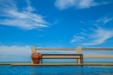 Wooden bench seat and pool on stone floor near sea and blue sky. 스톡 콘텐츠