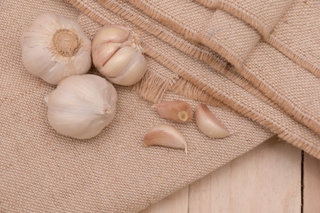 Organic garlic bulbs on burlap background.