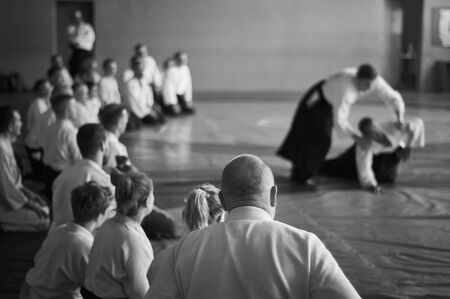 Aikido training. Black and white image. The teacher shows reception.  Traditional form of clothing in Aikido. 免版税图像