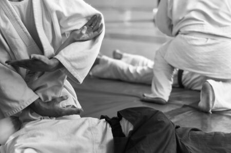 Black and white image of aikido. Hands of fighters. The traditional form of clothing in Aikido. Background image. No faces and recognizable elements