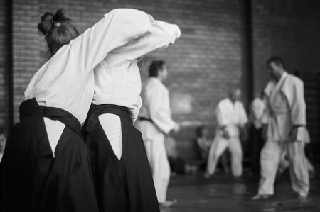 Black and white image of aikido. Àthlete girls involved in martial art of Aikido. The traditional form of clothing in Aikido.