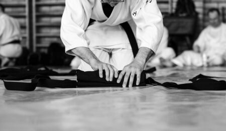 Black and white image of aikido. The male athlete carefully folds the black hackam. The traditional form of clothing in Aikido.