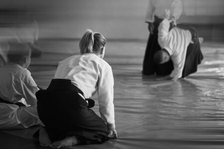 Aikido training. Black and white image. The teacher shows reception.  Traditional form of clothing in Aikido. Background image. No faces and recognizable elements! Banco de Imagens