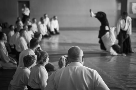 Aikido training. Black and white image. The teacher shows reception.  Traditional form of clothing in Aikido. Banco de Imagens