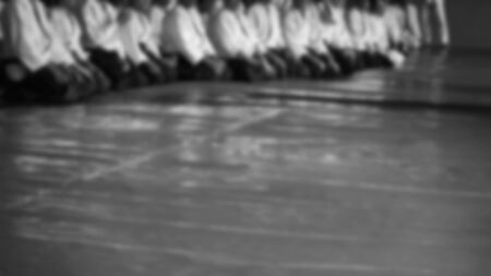 Black and white image of aikido. Men are sporsmen. Aikido workshop. A number of black belt practitioners in traditional uniform, white kimano and black hakama. Banco de Imagens