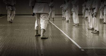 Kidss training on karate-do. Banner with space for text. For web pages or advertising printing. Photo without faces, from the back.