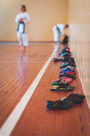 Shoes practiced at the entrance to the karate-do hall. Backdrop of a young girl in white clothes with a black belt. For web pages or advertising printing. Photo without faces