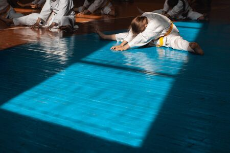 A teenager girl with a yellow belt in karate class is doing stretching. Beautiful morning light. Oriental martial arts. Childrens training. Banco de Imagens