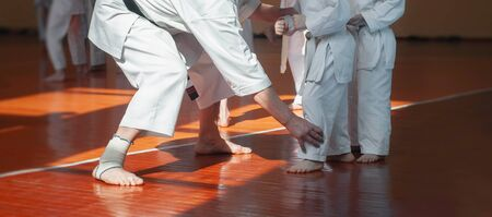 Kids training on karate-do. Teacher and students. Banner with space for text. For web pages or advertising printing. Photo without faces. Banco de Imagens