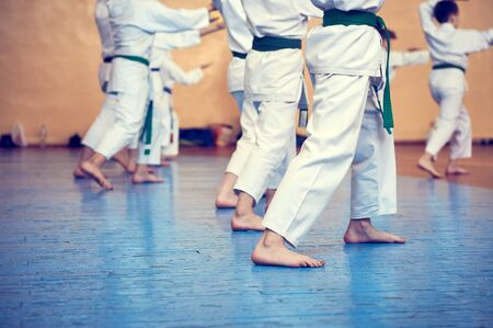 Kids training on karate-do. Young athletes in traditionally white kimonos with colored belts. Banner with space for text. Retro style. For web pages or advertising printing. Photo without faces. Imagens