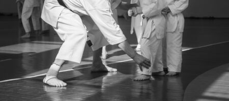 Kids training on karate-do. Teacher and students. Black and white banner with space for text. For web pages or advertising printing. Photo without faces. Banco de Imagens
