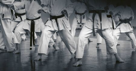 Kids training on karate-do. Banner with space for text. For web pages or advertising printing. Black and white photo without faces.