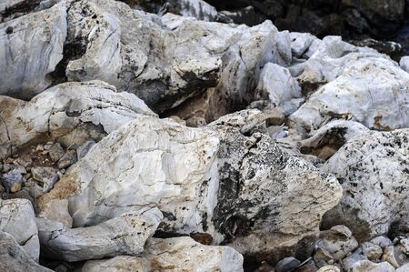 Raw stone on the coast of the Aegean. Texture of weathered, cracked stone. Gray with orange and black veins. Stock Photo