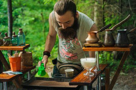 Karpaty, Ukraine, Shipot waterfall - July 20, 2019. A colorful Ukrainian man with a beard is making coffee in the sand outdoors near Shipot waterfall.